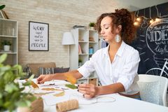 Designer Making Autumn Leaves Decoration. Portrait of mixed-race young woman choosing autumn leaves for interior decoration in modern apartment Stock Images