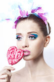 Portrait of a model with colorful make up and candy on white background Stock Photo