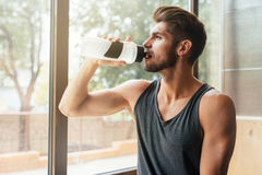 Portrait of model in gym. With bottle. sits on the table. near the window stock image
