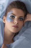 Portrait of a model laying between azure sheets Royalty Free Stock Images