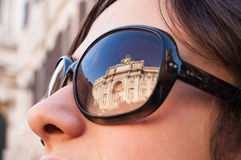 Portrait of a model with Trevi's fountain reflected on sunglasse. S Stock Image