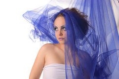 Portrait of a model with an unusual makeup. Portrait of a model with an unusual theatrical makeup in a blue headdress Stock Photo