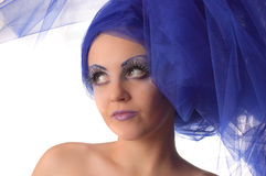 Portrait of a model with an unusual makeup. Portrait of a model with an unusual theatrical makeup in a blue headdress Stock Images