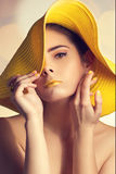 Portrait. Of a model in yellow hat with yellow lipstick and a golden ring Stock Image