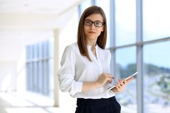 Portrait of modern business woman working with laptop computer in the office, copy space area stock photo