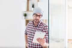 Portrait of modern businessman with tablet device opening office door royalty free stock image