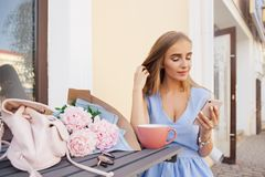 Portrait of modern fashion trendy women texting message by the smartphone in outdoor restaurant, waiting, dating. Portrait of modern fashion trendy woman texting stock photography