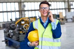 Female worker speaking by phone at factory. Portrait of modern female worker speaking by phone in workshop of industrial plant, copy space Stock Image