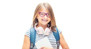 Portrait of modern happy teen school girl with bag backpack. Girl with dental braces and glasses isolated on white royalty free stock photos