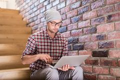 Portrait of modern hipster sitting on stairs and working on his laptop royalty free stock photos