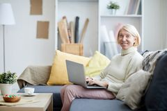 Mature Woman Using Laptop. Portrait of modern mature woman using laptop and looking at camera while sitting on sofa in office, copy space stock photos
