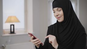 Portrait of modern muslim woman in traditional dress using smartphone and smiling. Positive lady in hijab using social