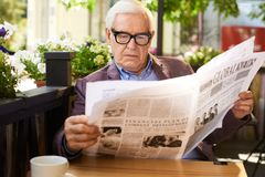 Senior Man Reading Newspaper oat Table in Cafe Royalty Free Stock Photography