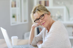Portrait of modern senior woman working on laptop stock images