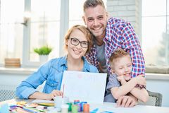 Happy Family Crafting Together. Portrait of modern young family posing with cute son and smiling happily sitting at drawing table together against big windows at Royalty Free Stock Photo