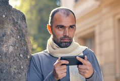 Portrait of modern young man with mobile phone in the street. Outdoor portrait of modern young man with mobile phone in the street Royalty Free Stock Photos