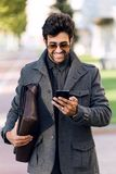 Modern young man using his mobile phone in the street. Royalty Free Stock Photography