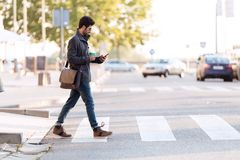 Modern young man using his mobile phone in the street. Stock Image