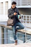 Modern young man using his mobile phone in the street. Royalty Free Stock Images