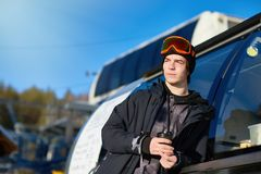 Modern Man at Ski Resort. Portrait of modern young man wearing snowboarding gear relaxing leaning on truck and warming up with coffee, copy space Stock Images