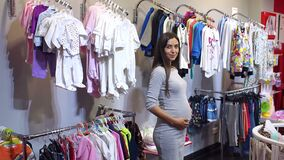 Pregnant woman choosing baby clothing in baby shop. Portrait of a modern young pregnant girl in a children`s clothing store stock video