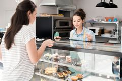 Young Woman Working in Cake Shop. Portrait of modern young women helping customer choosing desserts in cake shop or coffee house, copy space royalty free stock image