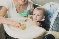 Portrait modifié la tonalité de beau bébé mangeant du gruau de la cuillère Photo stock