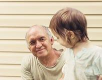 Portrait modifié la tonalité de grand-père heureux et de grandaughter jouant à Image stock