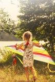 Portrait modifié la tonalité de peu d'enfant courant avec le cerf-volant au jour ensoleillé Image libre de droits