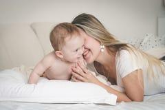 Portrait modifié la tonalité de rire la jeune mère avec ses 9 mois de fils de bébé sur le lit dans la chambre à coucher Photographie stock