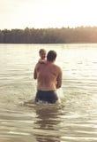 Portrait modifié la tonalité du père et de la fille jouant ensemble au lac Images libres de droits