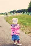 Portrait modifié la tonalité du petit enfant mignon marchant loin sur la route en avant Image libre de droits