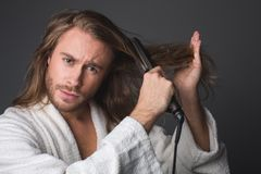 Stylish guy using hair straightener. Portrait of modish male arranging his hair, looking concerned. Isolated on grey background Stock Image