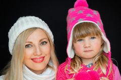 Portrait. Mom and daughter, in knitted hats, on a black background. Happy family, smiles and joy. stock photography