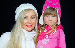 Portrait. Mom and daughter, in knitted hats, on a black background. Happy family, smiles and joy. stock photos