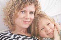 Portrait of mom and daughter. Portrait of young mom and daughter sitting on a bed and smiling stock photography