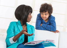 Portrait of mom helping son with homework. Stock Photo