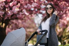 Portrait of mom stand with stroller in the park. Happy young mother walking with baby. Background of pink tree.  royalty free stock images