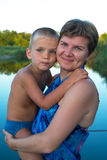 Portrait of a mom, who hugs his young son. Against the backdrop of a forest lake, on a wonderful summer evening. Happy mothers day in nature. Vertical image Royalty Free Stock Photos
