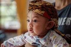 A portrait of a 3-month-old baby showing a smile and wearing Blangkon. Blangkon is a typical head covering of Java island made of stock photo