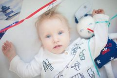 Portrait of 9 month old boy teething and posing in white cradle stock image