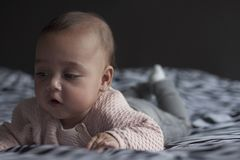Baby girl on bed focussing on hand stock images