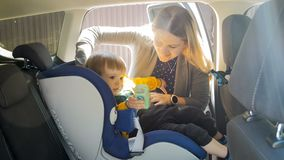 Portrait of young mother adjusting car child safety seat Stock Photo