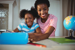Portrait of mother assisting daughter with homework Stock Images