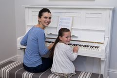 Portrait of mother assisting daughter in playing piano Stock Photos