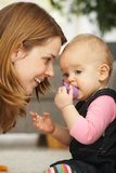 Portrait of mother and baby. Smiling mother leaning close to baby girl in closeup Royalty Free Stock Photos