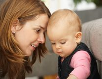 Portrait of mother and baby. Smiling mother leaning close to baby girl in closeup Royalty Free Stock Image