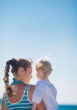 Portrait of mother and baby on beach. Rear view Stock Photos