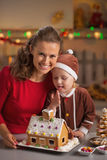 Portrait of mother and baby with christmas cookie house. Portrait of smiling mother and baby with christmas cookie house in kitchen royalty free stock photo