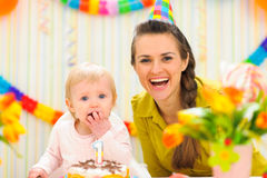 Portrait of mother with baby eating birthday cake Stock Image